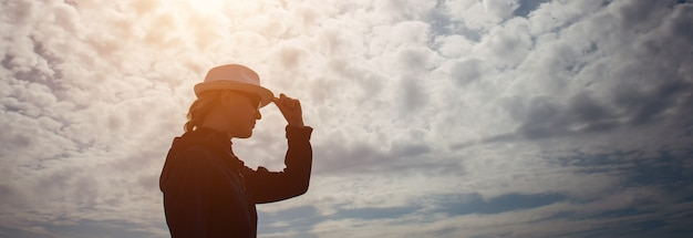 Женский силуэт в профиль со шляпой в руке на фоне таинственного неба с облаками