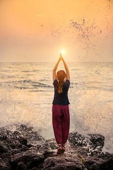ビーチで素晴らしい夕日にヨガ瞑想ポーズの女性のシルエット