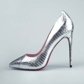 Female silver shoes on gray background