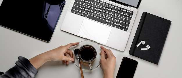 Female on simple workspace, holding coffee cup and looking on mock-up laptop