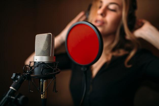 Female singer in headphones against microphone, song record in music studio.