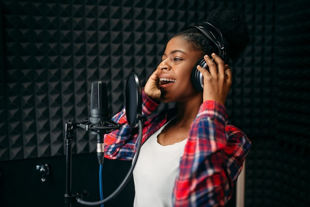 Female singer in headphones songs in audio recording studio.