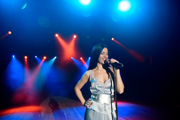 A female singer holding microphone against the colorful lights of the scene. bright colorful background with neon lights.