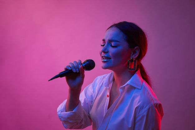 Певица в неоновом свете. девушка в белой рубашке с микрофоном. понятие о человеческих эмоциях, музыке.