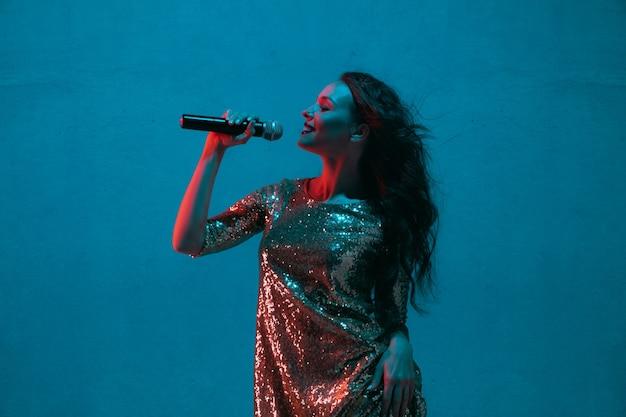 Female singer portrait isolated on blue studio wall in neon light