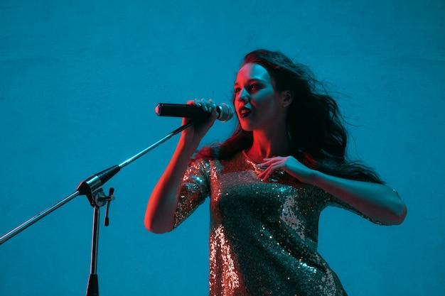 Ritratto di cantante femminile isolato sulla parete blu dello studio in luce al neon