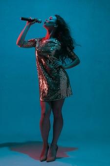 Портрет певицы, изолированные на синей стене студии в неоновом свете