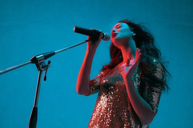 Портрет певицы, изолированные на синей стене студии в неоновом свете Бесплатные Фотографии