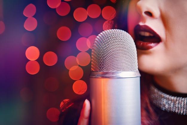 Певица с диско-микрофоном на светлом фоне боке крупным планом женских губ, окрашенных бордовым ...