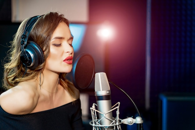 Female singer with headphones and closed eyes recording a song in studio.