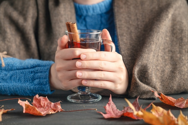 Female sit at home with hot drink in fall season