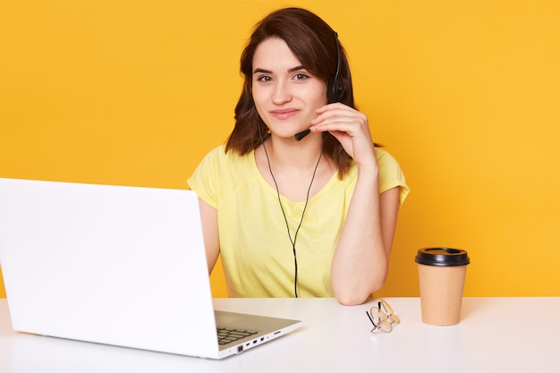Female sits at white desk with opened laptop computer, writes email, uses high speed internet, poses isolated on yellow, works or studies online. people and technology concept.