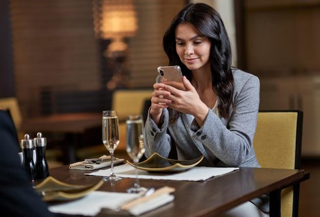 Женщина сидит за столиком в ресторане перед двумя бокалами шампанского, глядя на свой смартфон