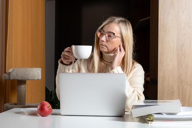 Женщина сидит за ноутбуком в домашнем офисе, пьет чай и задумчиво смотрит вдаль, задумчивая женщина отдыхает от работы