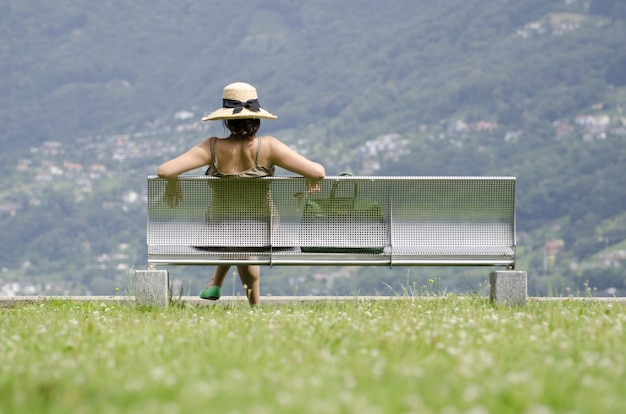 Donna seduta sulla panchina e ammirando la splendida vista delle montagne sfocate