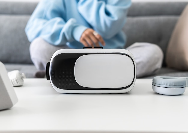 Female sitting on the couch in front of a table with virtual reality glasses, headphones