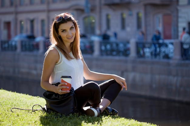 Female sitting on the grass drinking coffee in a cardboard cup