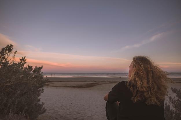 Женщина сидит на берегу моря и смотрит на закат