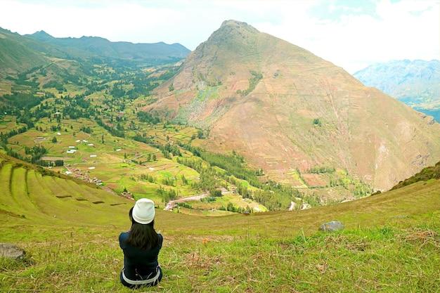 ピサック考古学公園の山に座っている女性インカスクスコペルーの聖なる谷