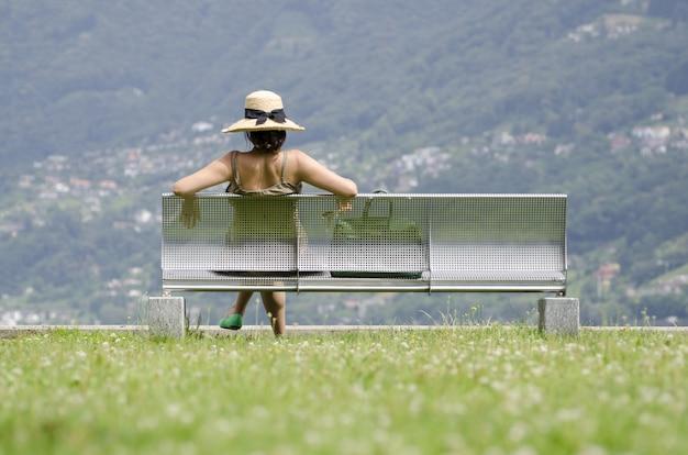 Женщина сидит на скамейке и любуется прекрасным видом на размытые горы