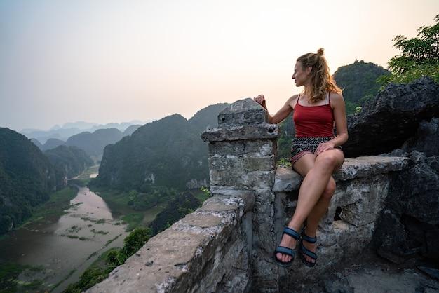 전망을 즐기는 벽의 가장자리에 앉아 있는 여성