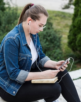 Female sitting in park using smartphone