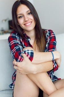 Female sitting on sofa and and smiling