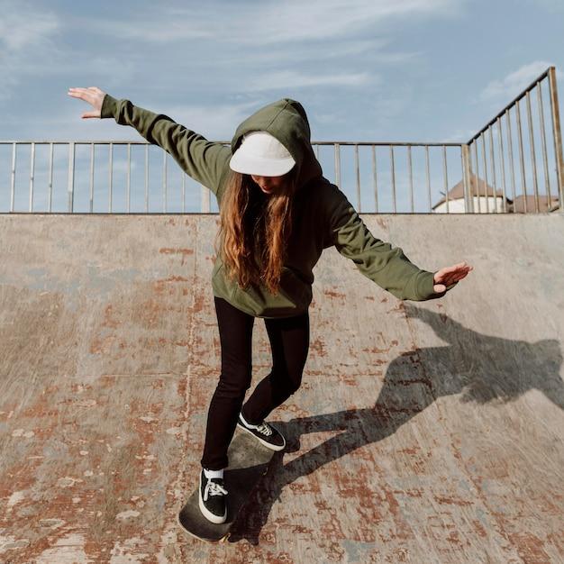 트릭을 위해 경사로를 사용하는 여성 스케이트 보더
