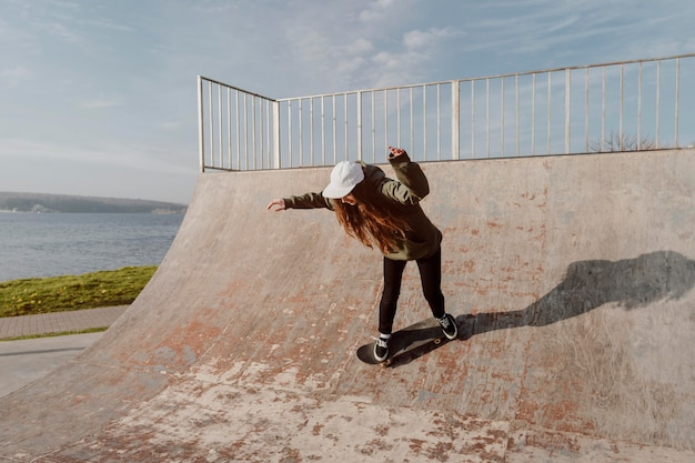 Skateboarder femminile che utilizza rampe per i trucchi