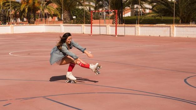 코트에서 한쪽 다리에 웅크 리고 균형을 잡는 여성 스케이팅 선수