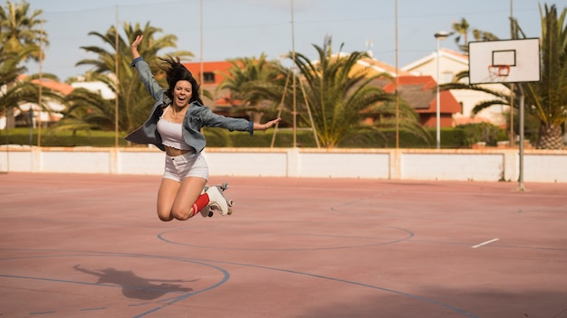 Female skater jumping over the football court