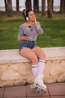 A female skater listening music on headphone