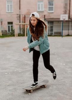Pattinatore femminile che pratica lo skateboard all'aperto