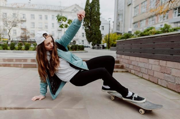 屋外でスケートボーディングを練習している女性スケーター