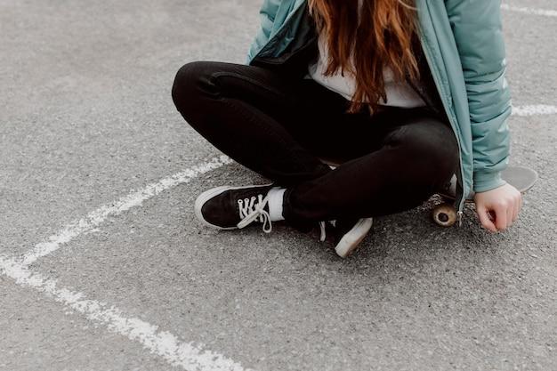 Pattinatore femminile che si siede accanto al suo skateboard all'aperto