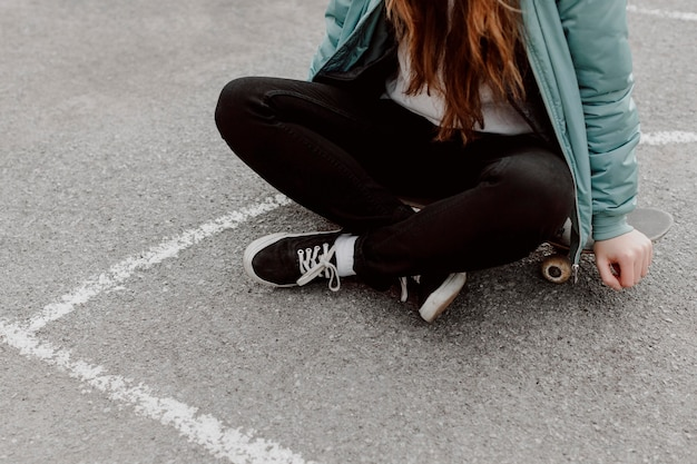 屋外でスケートボーディングの隣に座っている女性スケーター
