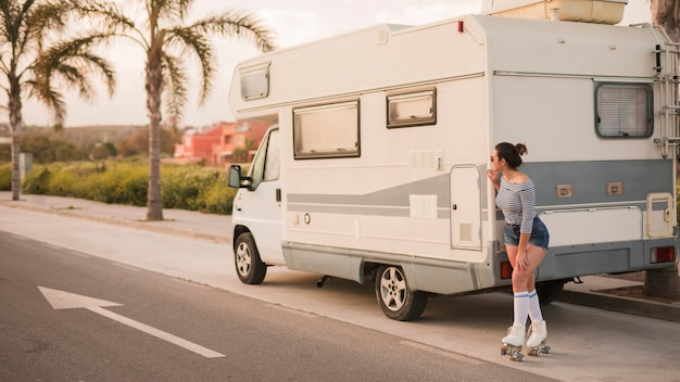 Female skater standing behind the caravan on road peeking