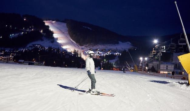 スキーの上に立ってスキーの日を過ごした後の女性スキーヤー