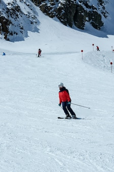 Female skier in downhill slope. winter sport recreational activity