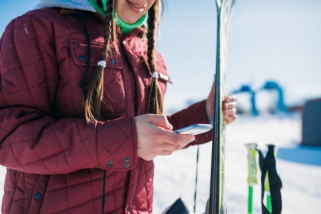 女性スキーヤーはスキーと携帯電話を手に持っています。冬のアクティブなスポーツ、極端なライフスタイル。ダウンヒルまたはマウンテンスキー