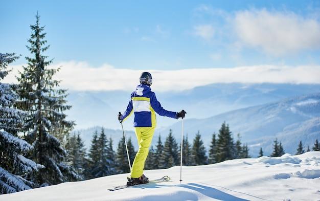 雪山の頂上で女性スキーヤー