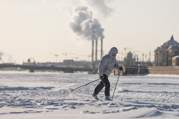Female skier riding on ice of the frozen neva river at sunny day, early spring in st. petersburg, annunciation bridge on surface. winter sports in an urban setting