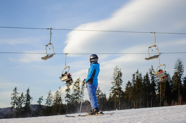 Female skier standing on a ski slope at a sunny day with ski-lift, forest and beautiful sky on the background