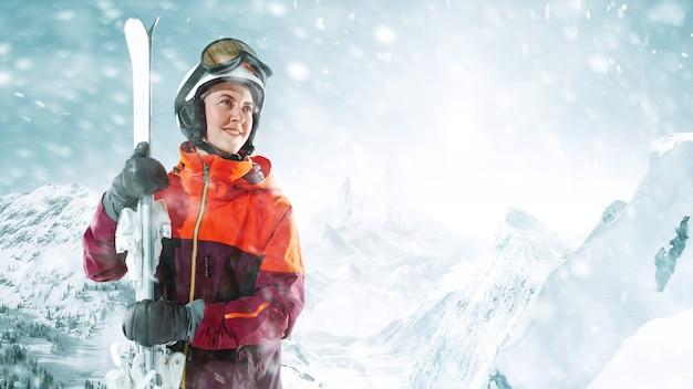 美しい山の風景を背景に片手に空を持って立っている女性スキーヤー。冬、スキー、雪、休暇、スポーツ、レジャー、ライフスタイルの概念