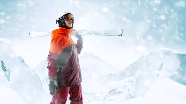 美しい山の風景の背景に片手で空と立っている女性スキーヤー。冬、スキー、雪、休暇、スポーツ、レジャー、ライフスタイルの概念