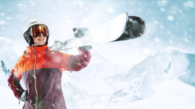 美しい山の風景の背景に片手で空と立っている女性スキーヤー