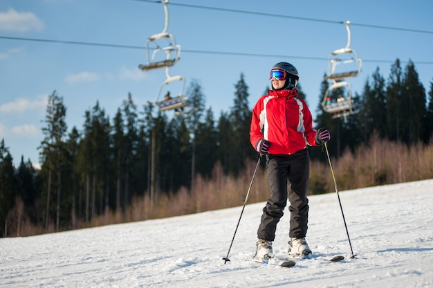 Female skier standing with skis on snowy slope in sunny day