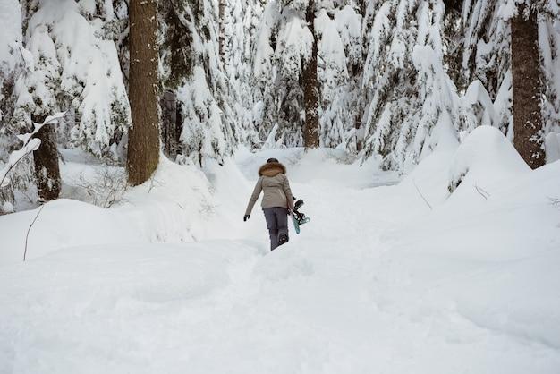 雪景色をスキーで歩く女性スキーヤー