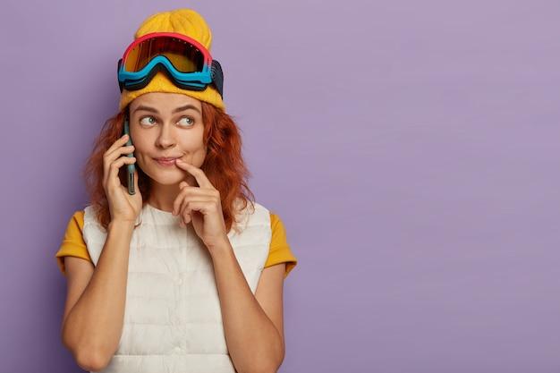 Sciatore femminile con i capelli rossi fa una telefonata, guarda da parte con espressione pensierosa, riceve un buon suggerimento, isolato sul muro viola