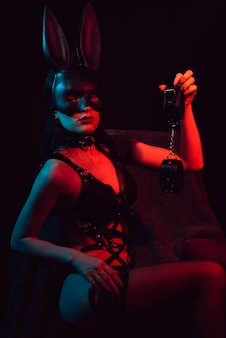Female slave in sexy lingerie with bunny mask with leather handcuffs